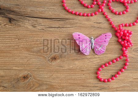 A string of pink beads displayed with a butterfly made out of silk on a wooden background