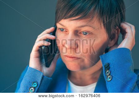 Worried businesswoman during unpleasant telephone conversation with mobile phone