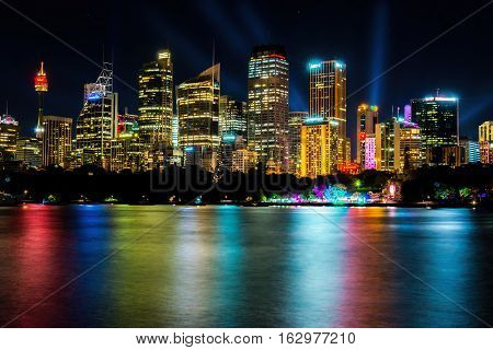 Sydney, Australia - May 29, 2016: Long exposure of city skyline by night from Mrs Macquarie's Chair, featuring light show. High resolution vibrant image with colorful water reflections.