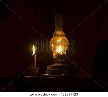kerosinaovaya lamp and a candle flickering in the dark