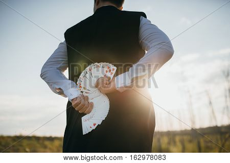 magician in a suit with cards at sunset