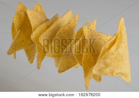 Row of corn made chips on white background