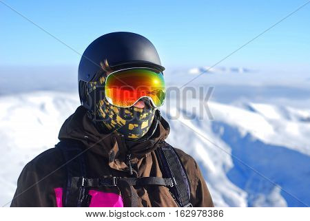 Portrait of a boy in a protective helmet and snowboard mask against the backdrop of snow-capped mountains