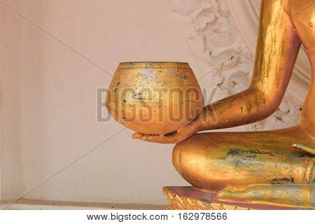 hand hold alms bowl of buddha statue ancient golden in the Thai temple