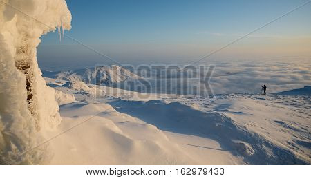 Photographer are making landscape shot with help of tripod. Photographer silhouette is outlined against white clouds background. Sunrise scene in winter mountains.