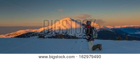 Photographer are making landscape shot with help of tripod. Sunlit mount Petros in background. Sunrise scene. Panorama.