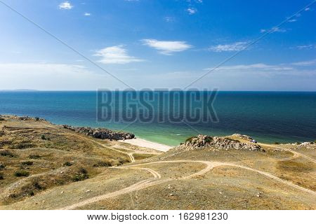 hilly sea coast with rocks and sky with clouds