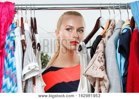Thoughtful sad blonde woman stand near wardrobe rack full of clothes portrait. Retail business beauty store modern leisure urban life boutique and mall visiting occasion nothing to wear concept