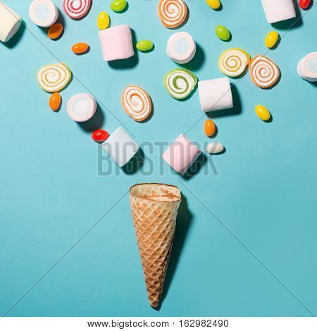 Top view of pastel colored marshmallow and sweet candy in a waffle cup waffle cones with candy