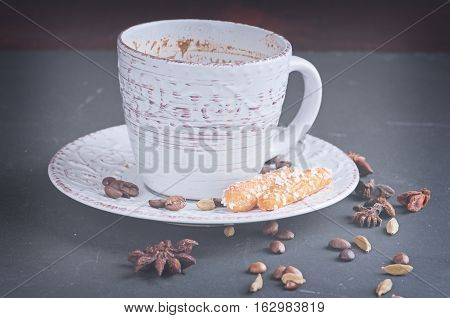 a sugar homemade biscuits piled in a wicker basket and a cup of hot coffee on a dark background