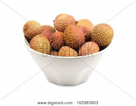 Many ripe litchi fruits isolated in white bowl front view closeup