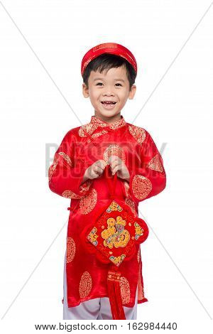 Vietnamese boy cuddling stuffed carp. Portrait of a handsome Asian baby boy on traditional festival costume. Cute little Vietnamese boy in red ao dai dress smiling. Text mean Happiness