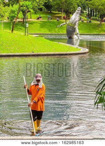 KUALA LUMPUR, MALAYSIA - JANUARY 12, 2014: Man cleans garden pond in The KLCC Park, public park located near Petronas Twin Towers. Kuala Lumpur, Malaysia