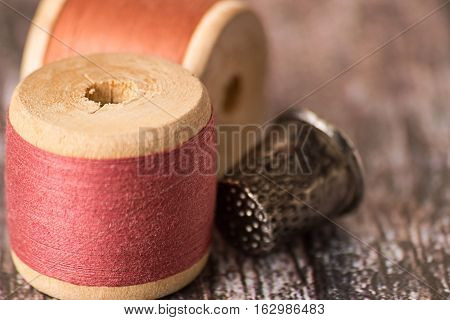 Old wooden coils with color sewing thread and a thimble on a wooden background.
