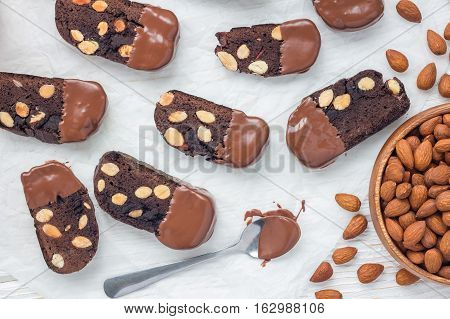 Homemade dark chocolate biscotti cookies with almonds covered with melted chocolate horizontal top view