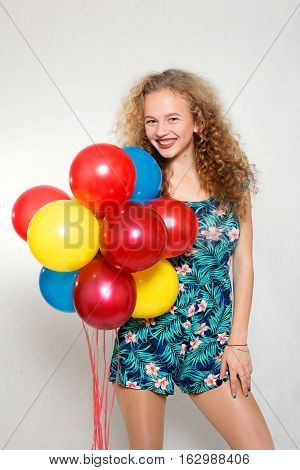 people teens holidays and party concept - happy smiling pretty teenage girl with helium balloons over gray background beautiful girl with curly hair
