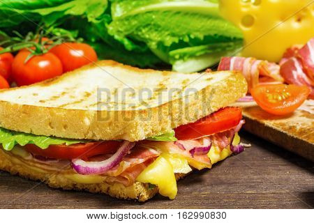 grilled sandwich or panini with bacon cheese lettuce onion tomatoes and ingredients on rustic wooden table. shallow depth of field