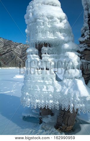 Strange form Icicles on tree on a background of mountains in the lake