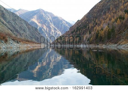 Peaks reflecting in mountain lake like in a mirror, autumn forest