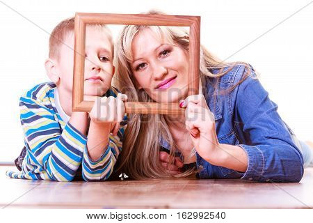 Spending time family bonds parenthood. Mother and son have fun play with empty picture frame hold in hand lay on floor.