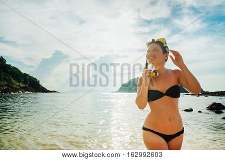 Happy snorkeling at the beach. Beach vacation snorkel girl snorkeling with mask. Bikini woman relaxing on summer tropical getaway doing snorkeling activity with snorkel tuba sun tanning.