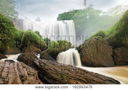 Bottom view of waterfall with yellow water among green woods on dramatic sky background in Vietnam. The Elephant waterfall is a popular tourist destination of Asia.