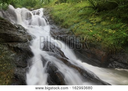 Bottom view of amazing Datanla waterfall with crystal clear water among green woods in summer