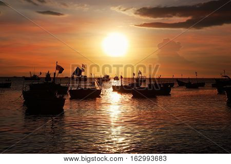 Dark silhouettes of Vietnamese round fishing boat-baskets in the setting sun. Mui Ne Vietnam