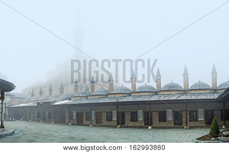 KONYA TURKEY - JANUARY 20 2015: The courtyard of Mevlana Museum with the view on the living chambers of dervishs and the silhouette of the Selimiye Mosque in fog on January 20 in Konya.