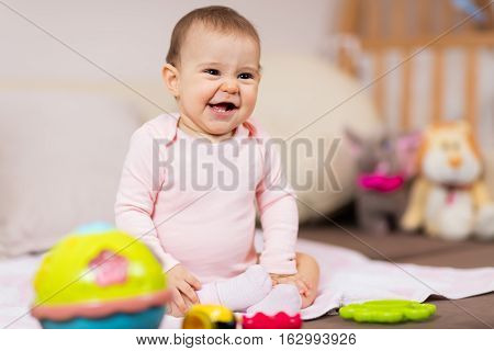 Baby girl having fun at home. Playful baby girl playing with her toys on the bed.