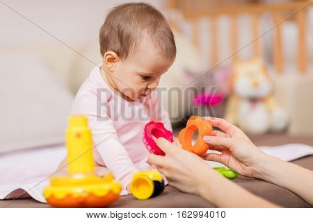 Young mom playing with baby girl. Making playtime fun and engaging