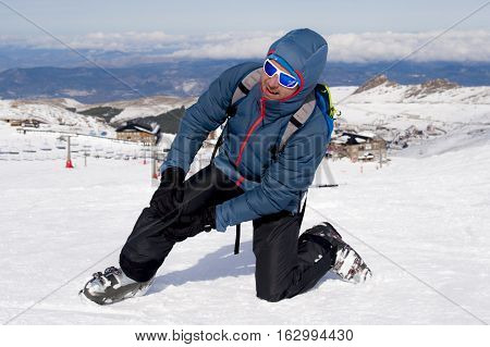 young man lying on cold snow after ski crash holding his injured knee in pain at Sierrna Nevada resort in Spain with mountains background in winter sport accident and injury concept