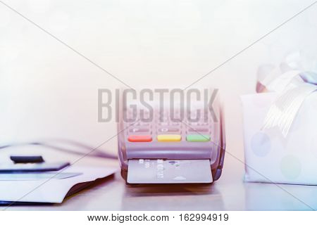 Credit card and card reader machine, on table with gift box background