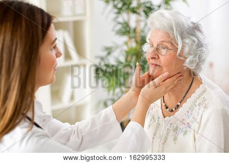 Beautiful Young Doctor Examining Senior Woman Lymph Glands