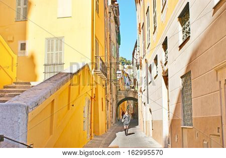 MENTON FRANCE - FEBRUARY 22 2012: The tall mediterranean houses painted in bright colors decorate the maze of narrow streets of old town on February 22 in Menton.