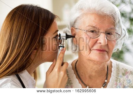 Young Beautiful Doctor Holding Otoscope And Examining Patient Ear