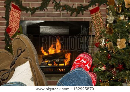 A husband and wife relaxing by the fireplace during the holiday season.