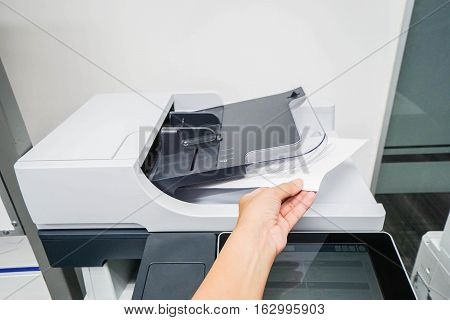 woman bring printed documents from printer machine with left hand