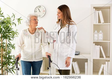 Beautiful young doctor helping senior woman walking with a walker in clinic