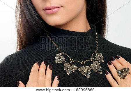 studio portrait long hair model demonstrated stylish necklace and finger ring. Spring collection accessory and jewelry