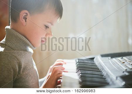 A boy plays on an electric synthesizer