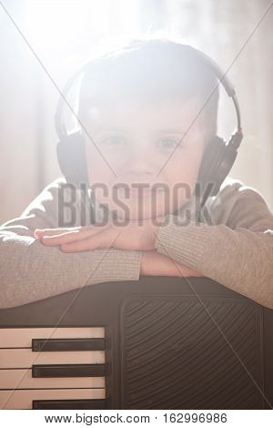 Boy listening to music with headphones leaning on the synth