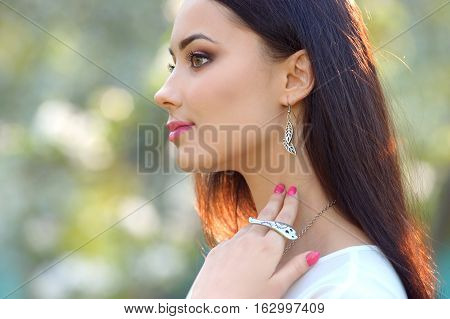 close-up portrait fashion model young woman with luxury accessory and jewelry. Close-up beauty portrait with jewelry outdoors