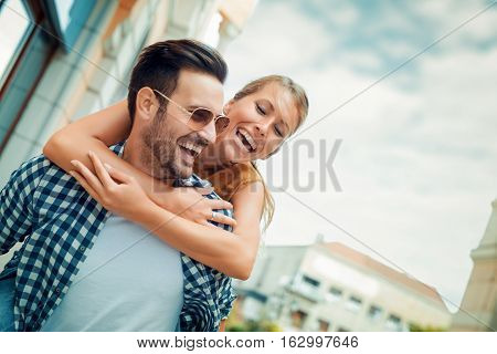 Man giving piggyback ride to woman in the city.