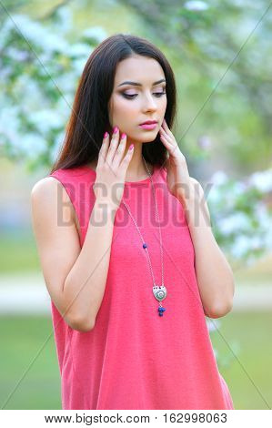 long hair beauty model demonstrated spring collection jewelry. Blooming garden background