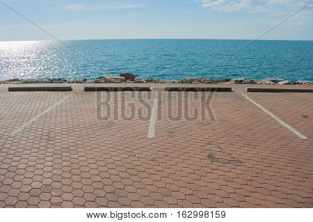 Empty car parking space with sea and blue sky background.