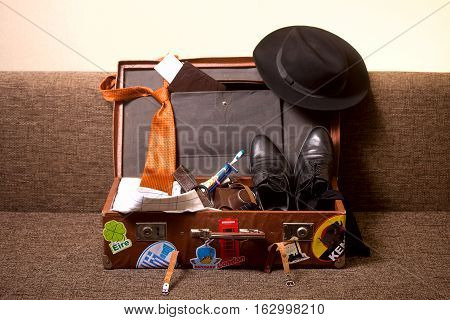 Gathering business men to travel. The shabby, battered suitcase with stickers of the countries visited all the essentials.