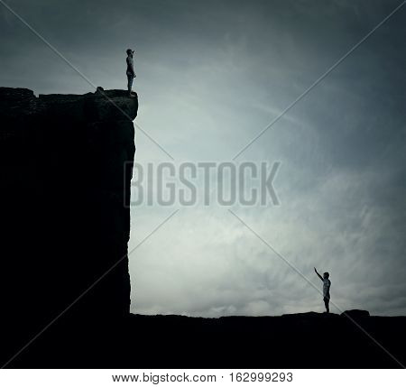 Conceptual image with two lost persons standing on a cliff at different hights trying to find each other. Parallel world alternate reality multiverse fiction theory and relativity. Human life cycle highs and lows.