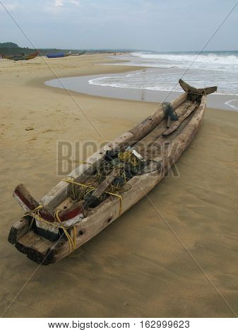 Old fishing boat on the beach.  Chowara, Kerala, South-west India.