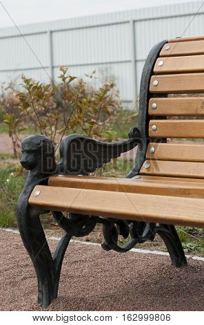 iron armrest in bench decorated head of lion with wing